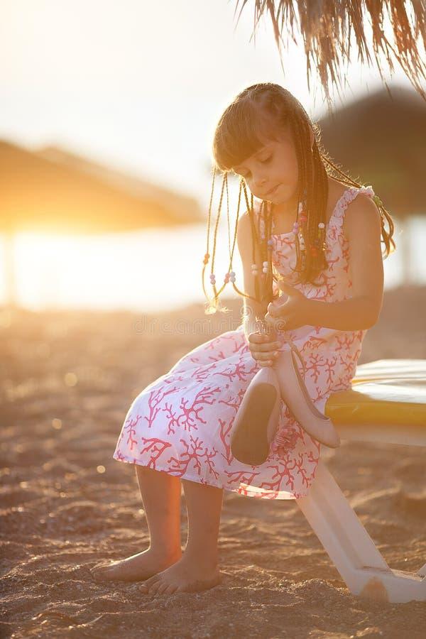 Menina bonita pequena que senta-se na praia no por do sol fotografia de stock royalty free