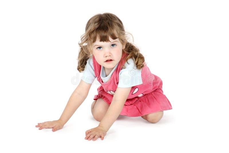 A menina bonita pequena senta-se no assoalho imagem de stock