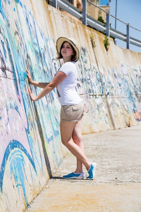 Menina bonita perto da parede com grafittis imagens de stock royalty free