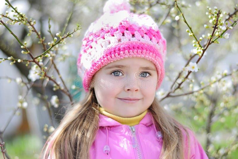 A menina bonita perto de uma árvore de florescência foto de stock royalty free