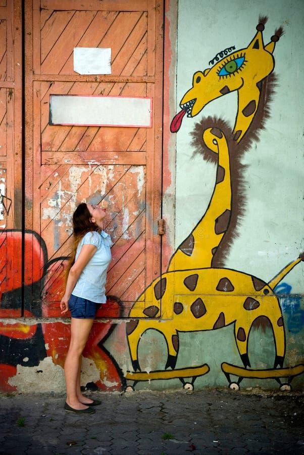 Menina bonita perto dos grafittis engraçados foto de stock royalty free