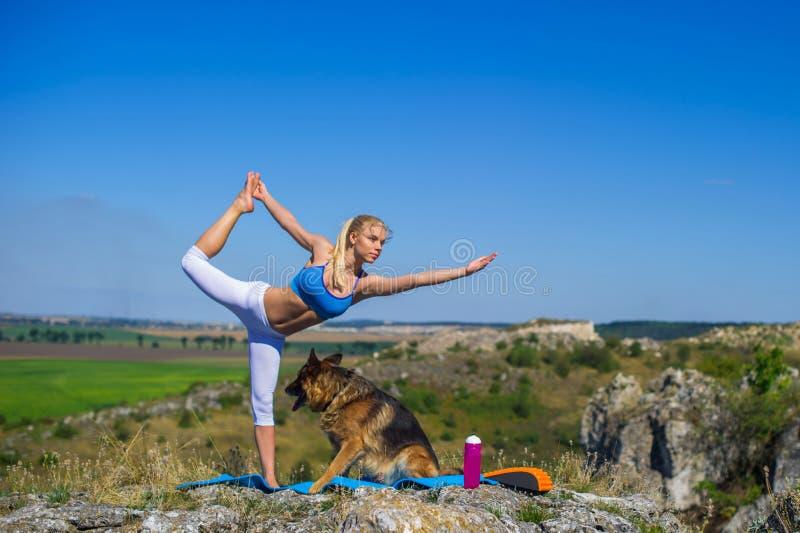 A menina bonita pratica a ioga com cães, pastor alemão imagens de stock