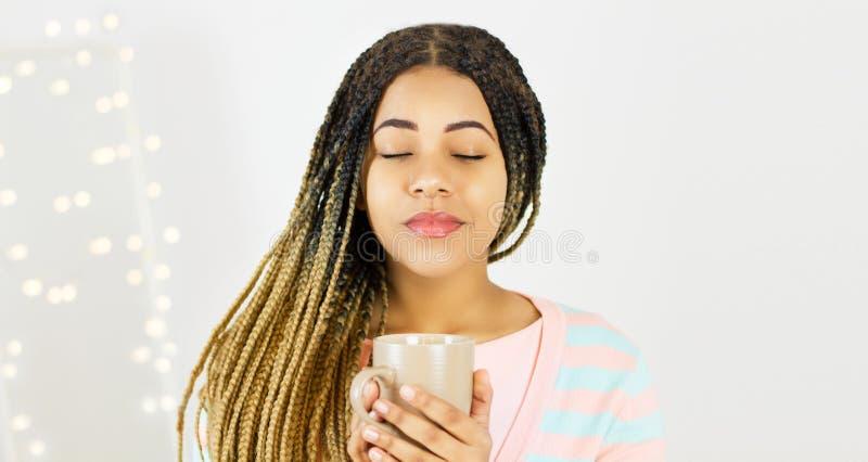 Menina bonita preta que aprecia uma bebida quente em casa no fundo do bokeh fotografia de stock royalty free