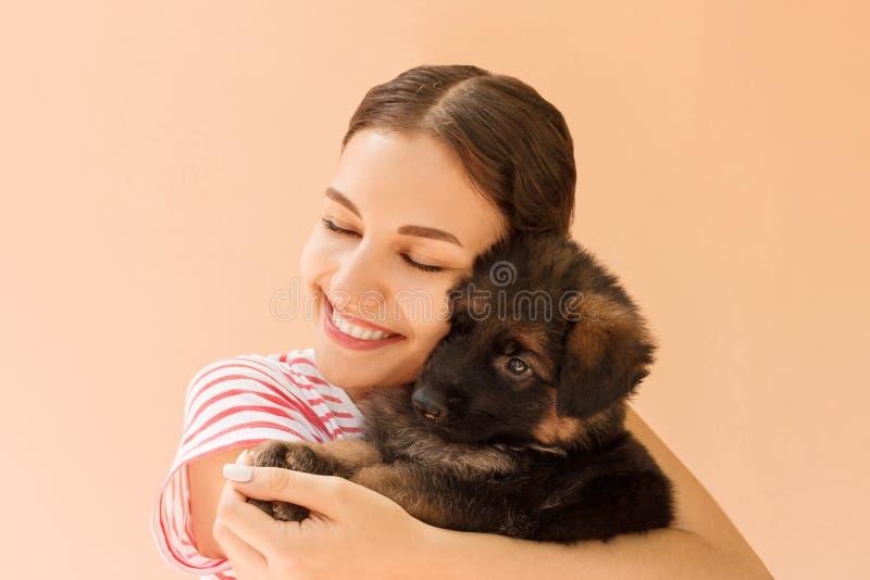 Menina bonita que abraça firmemente seu cachorrinho pequeno bonito imagem de stock royalty free