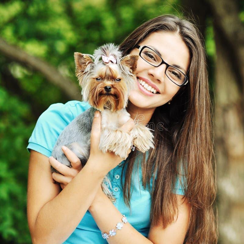 Menina bonita que abraça o cachorrinho pequeno foto de stock royalty free