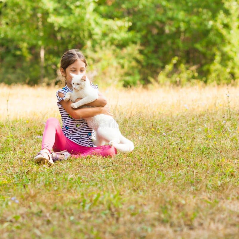 Menina bonita que abraça seu gato branco doméstico imagens de stock royalty free