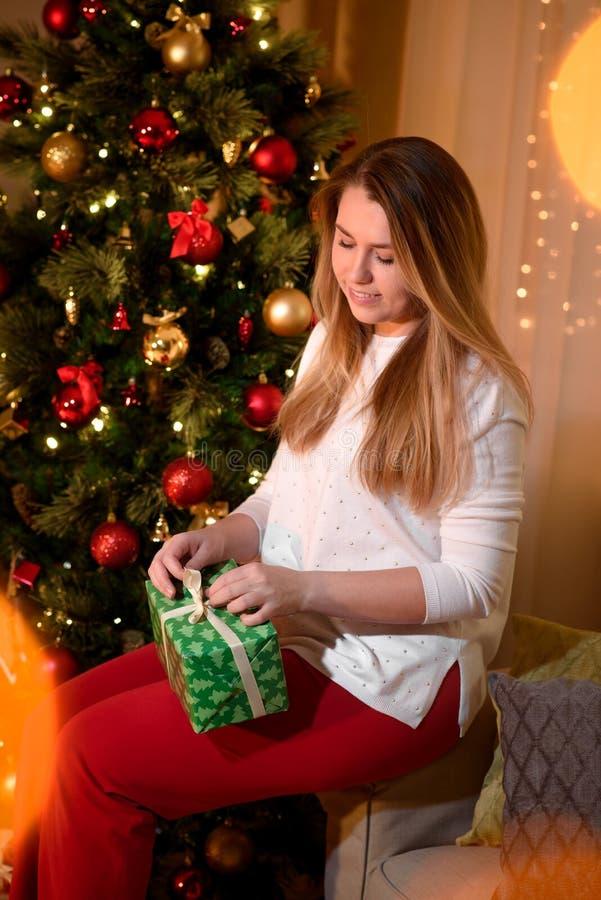 Menina bonita que abre um presente do feriado fotografia de stock