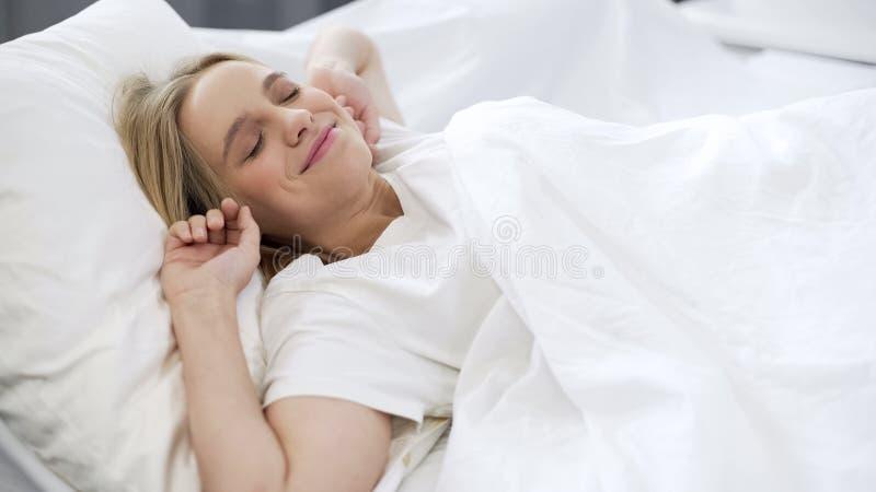 Menina bonita que acorda na manhã, esticando-se após o sono saudável foto de stock