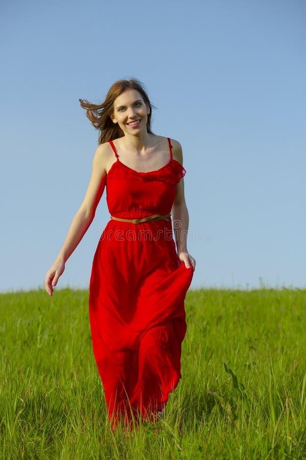 Menina bonita que anda com um vestido vermelho fotos de stock