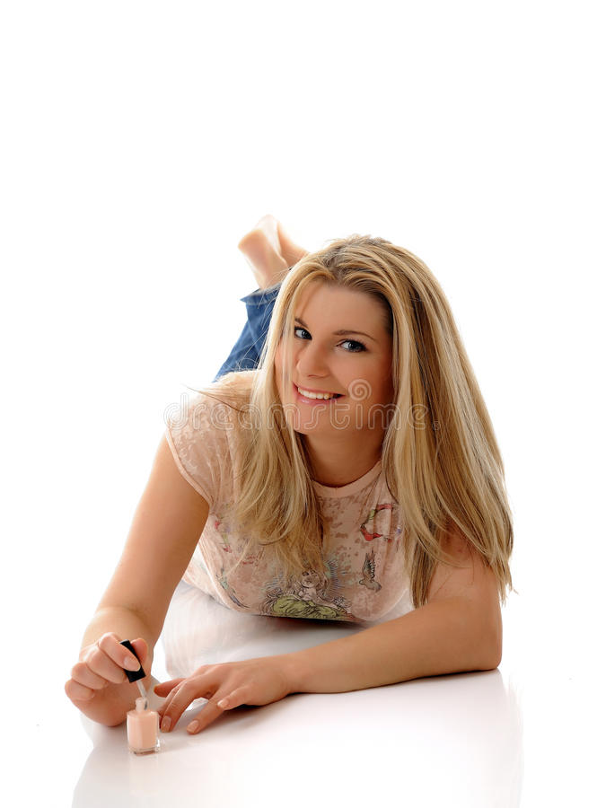 Menina bonita que aplica o lustrador de prego imagem de stock royalty free