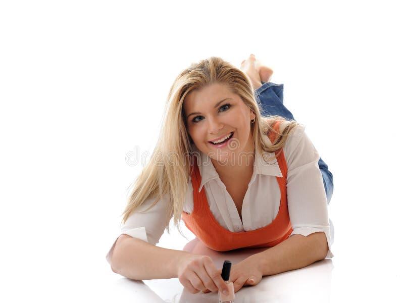 Menina bonita que aplica o lustrador de prego fotografia de stock royalty free