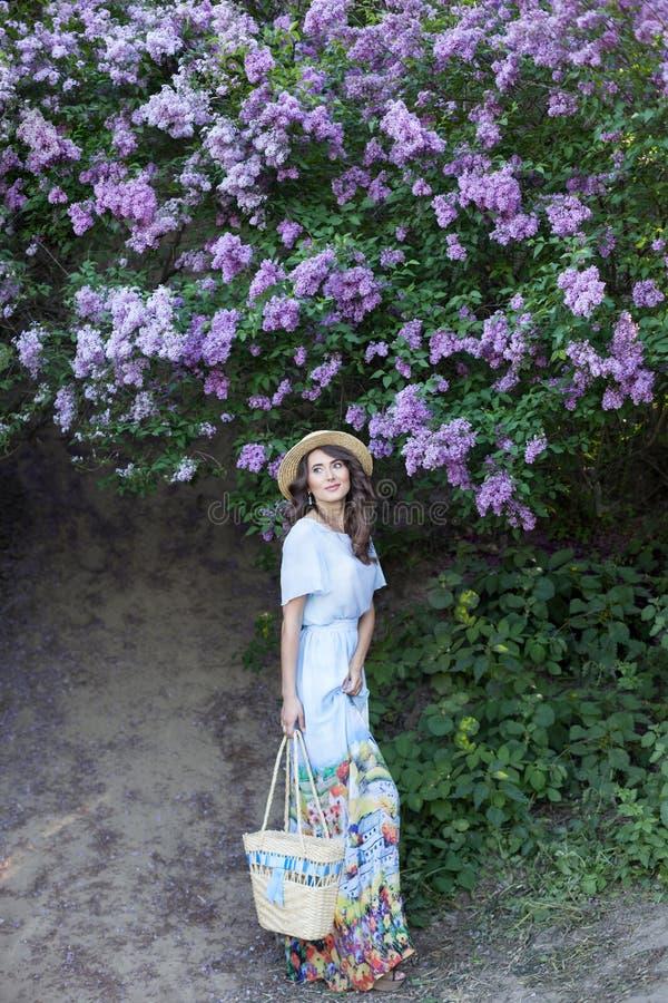 Menina bonita que aprecia o cheiro do lilás em um dia de verão Conceito da aromaterapia e da mola Uma menina bonita, uma mulher b imagens de stock
