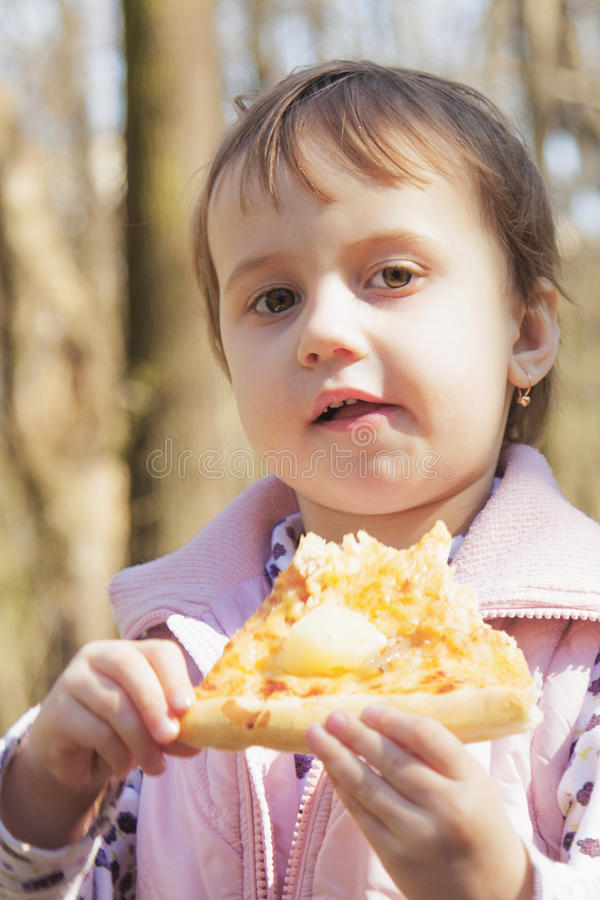Menina bonita que aprecia um alimento delicioso da pizza fora, imagens de stock royalty free