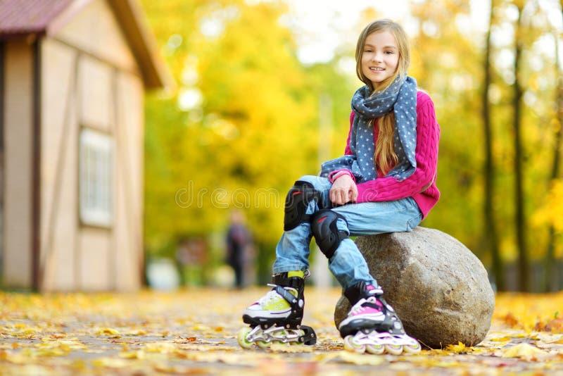 Menina bonita que aprende ao patim de rolo no dia bonito do outono em um parque fotos de stock