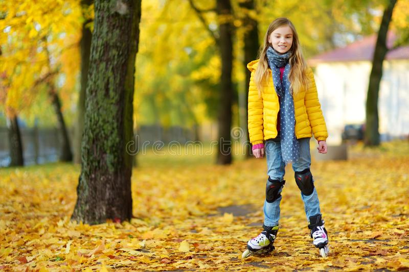 Menina bonita que aprende ao patim de rolo no dia bonito do outono em um parque fotografia de stock