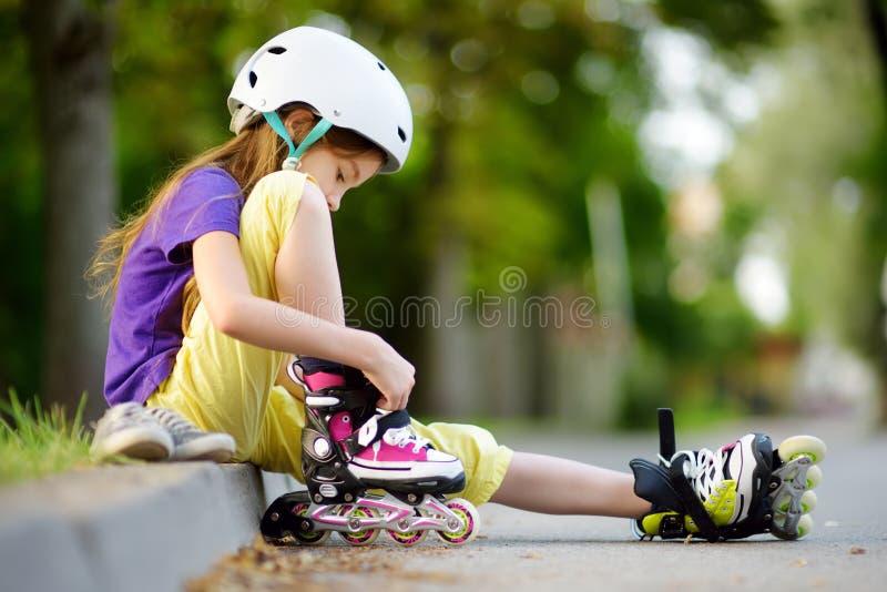 Menina bonita que aprende ao patim de rolo no dia de verão bonito em um parque fotografia de stock royalty free