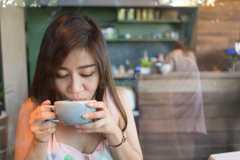 Menina bonita que bebe o café ou o chá quente no café do café fotos de stock