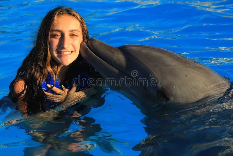 Menina bonita que beija golfinhos felizes de sorriso de um nariz da garrafa da nadada da criança da cara da aleta lindo do golfin imagens de stock royalty free