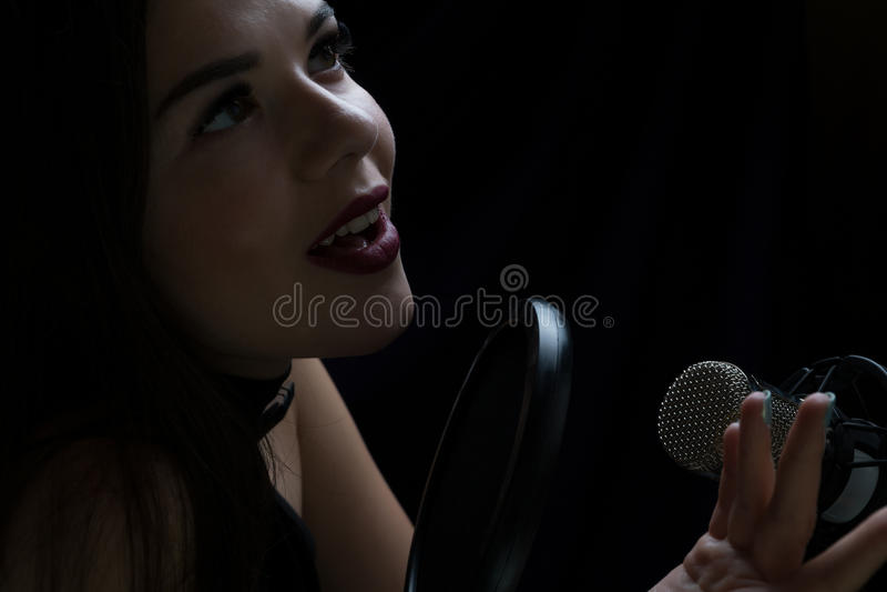 Menina bonita que canta no estúdio de gravação com microfone imagem de stock