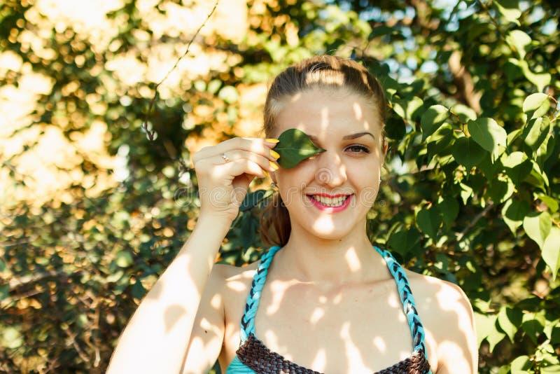 Menina bonita que cobre um olho pela folha verde foto de stock royalty free