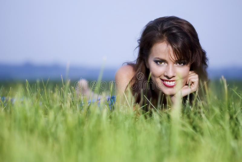 Menina bonita que coloca na grama fotos de stock royalty free