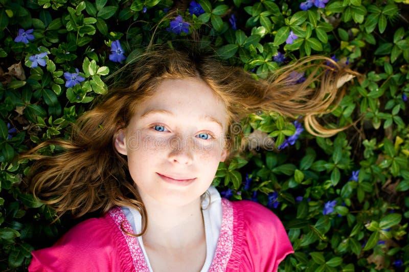 Menina bonita que coloca na planta da pervinca imagens de stock
