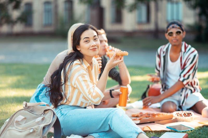 Menina bonita que come com seus groupmates no piquenique imagens de stock royalty free