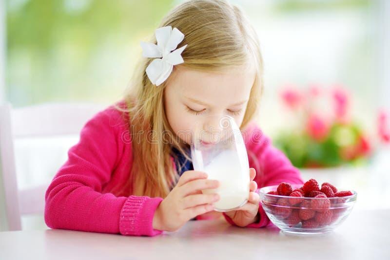 Menina bonita que come framboesas e o leite bebendo em casa Criança bonito que aprecia seus frutos frescos e bagas saudáveis fotos de stock