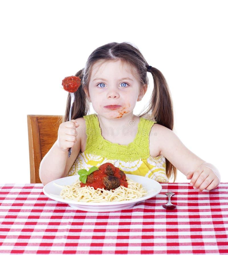 Menina bonita que come a massa e os meatballs foto de stock