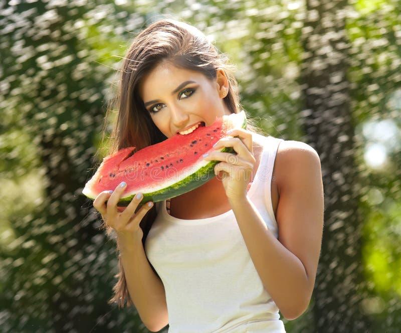 Menina bonita que come a melancia fresca Tem uma boa pele delicada, seu voo do cabelo, e sorri Comer feliz da jovem mulher imagem de stock