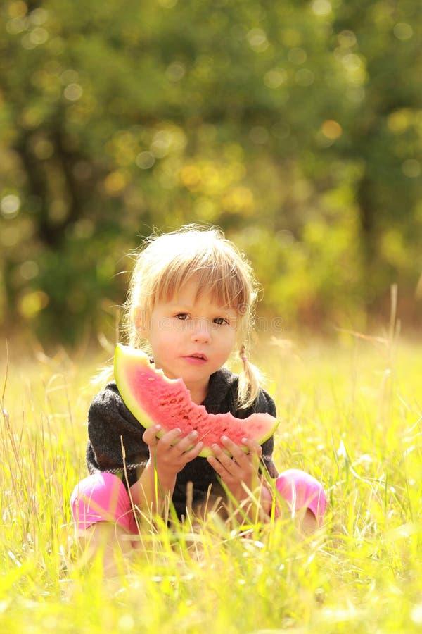Menina bonita que come a melancia na natureza imagens de stock