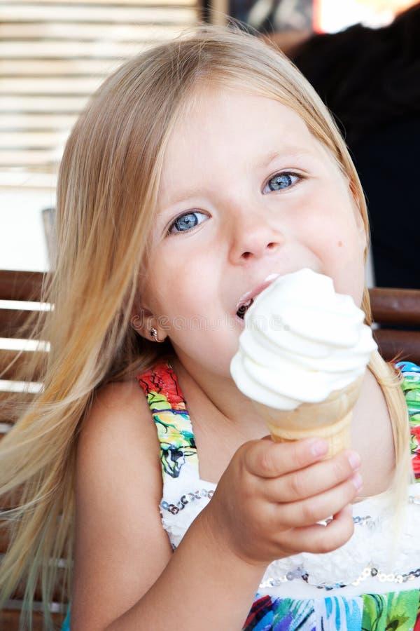 Menina bonita que come o gelado ao ar livre fotos de stock royalty free
