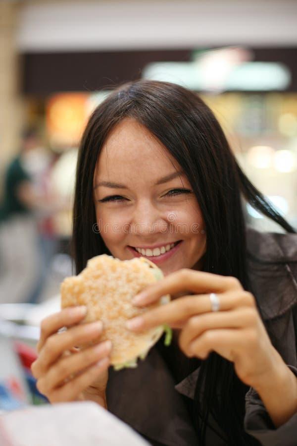 Menina bonita que come o hamburguer imagem de stock