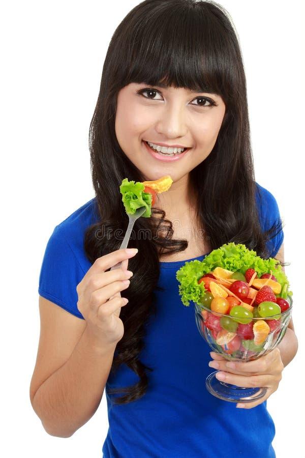 Menina bonita que come a salada de fruta, fazendo dieta fotos de stock