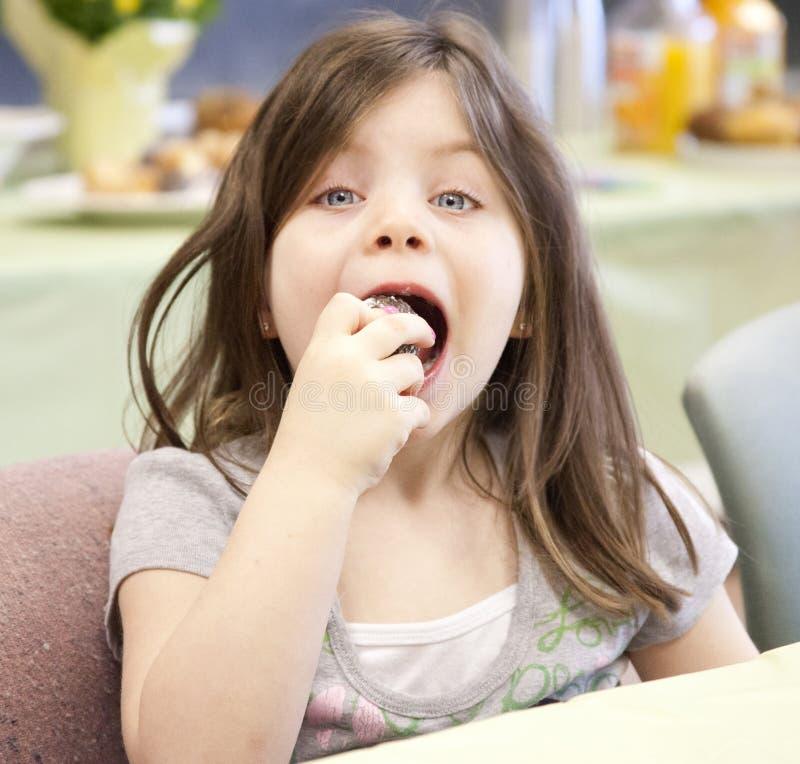 Menina bonita que come uma filhós fotos de stock royalty free