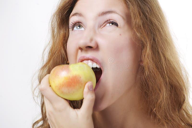 Menina bonita que come uma maçã imagens de stock