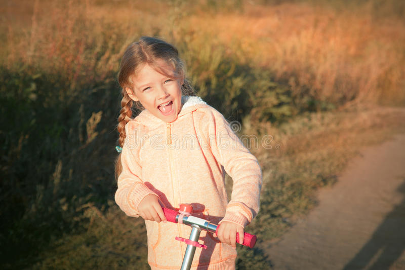 Menina bonita que conduz o 'trotinette' na estrada rural foto de stock royalty free