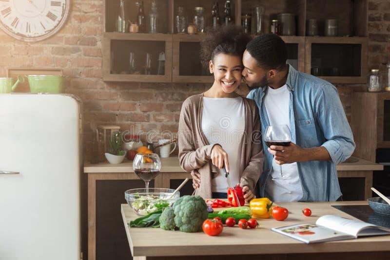 Menina bonita que cozinha quando seu noivo que beija a no mordente fotos de stock