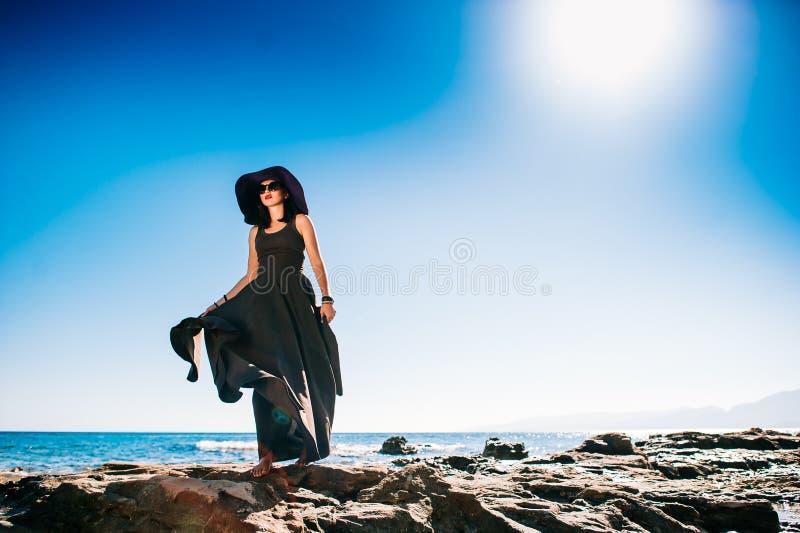 Menina bonita que descansa em uma rocha na costa de mar imagens de stock royalty free
