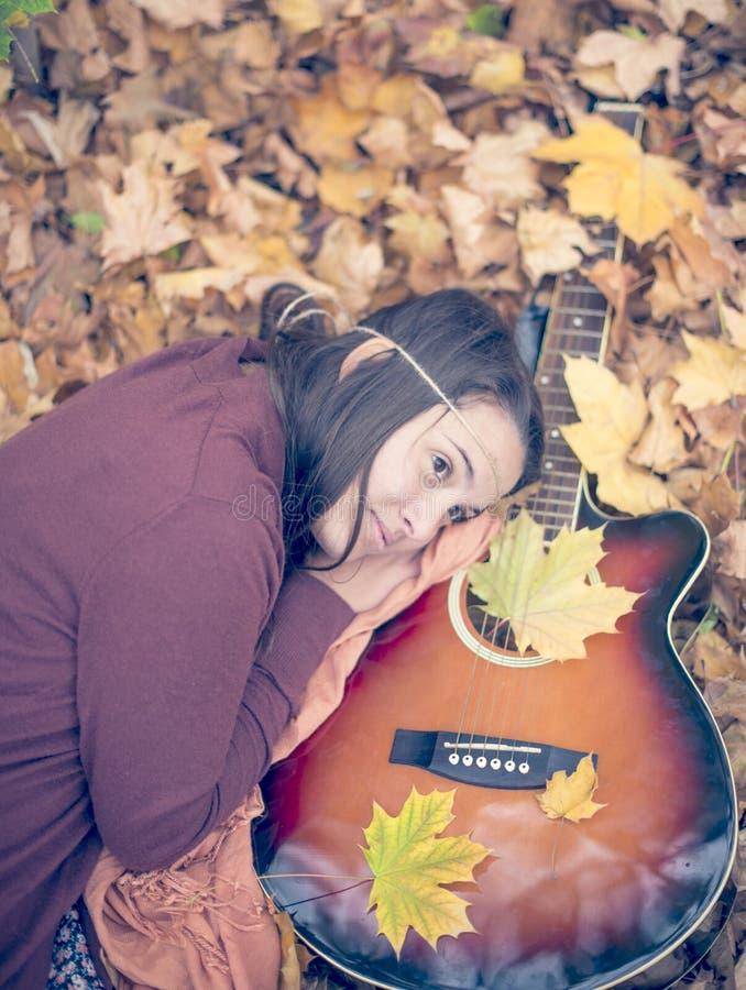 Menina bonita que descansa nas folhas do outono imagem de stock