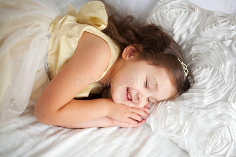 Menina bonita que dorme e que sorri em seu sono. imagens de stock royalty free