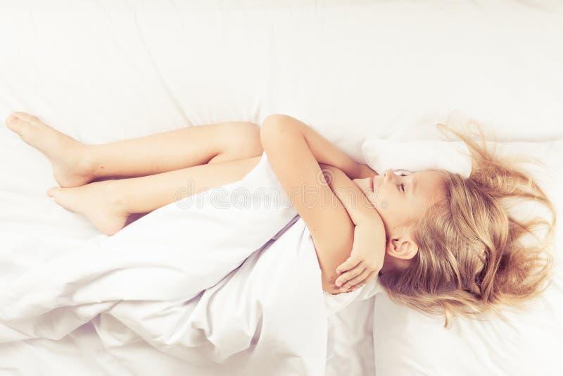 Menina bonita que dorme na cama foto de stock