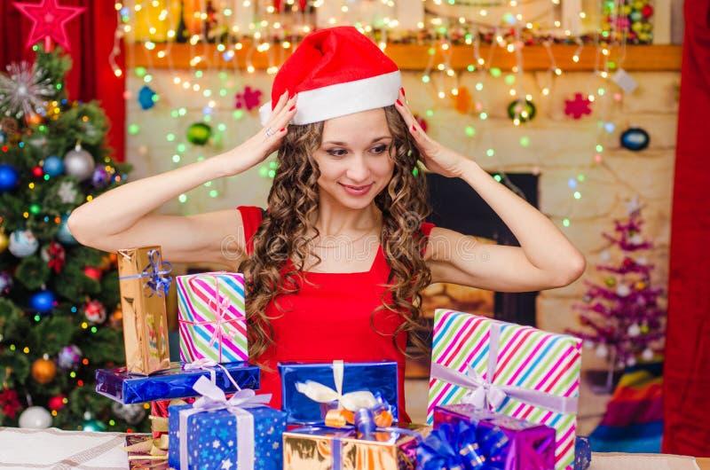 Menina bonita que embreia sua cabeça ao escolher um presente imagens de stock