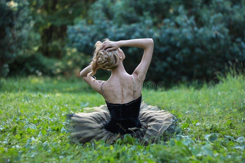 Menina bonita que encontra-se e que descansa em uma grama no parque do verão fotos de stock