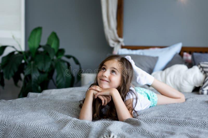Menina bonita que encontra-se na cama na casa imagem de stock royalty free
