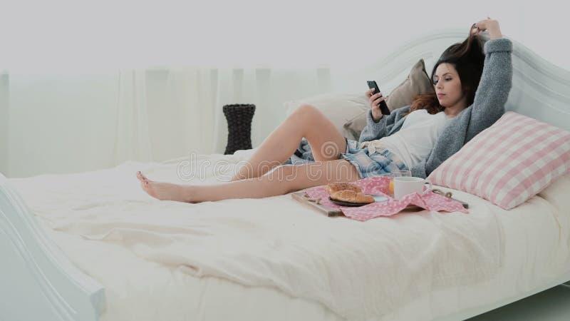 Menina bonita que encontra-se na cama na manhã e que usa o smartphone Jovem mulher que datilografa, consultando o Internet e boce imagem de stock