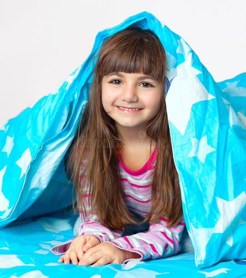Menina bonita que encontra-se na cama sob uma cobertura azul imagens de stock
