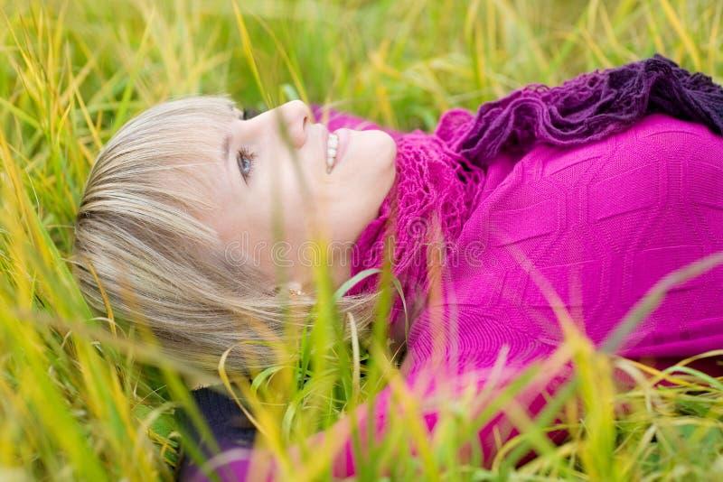Menina bonita que encontra-se na grama da queda fotografia de stock royalty free