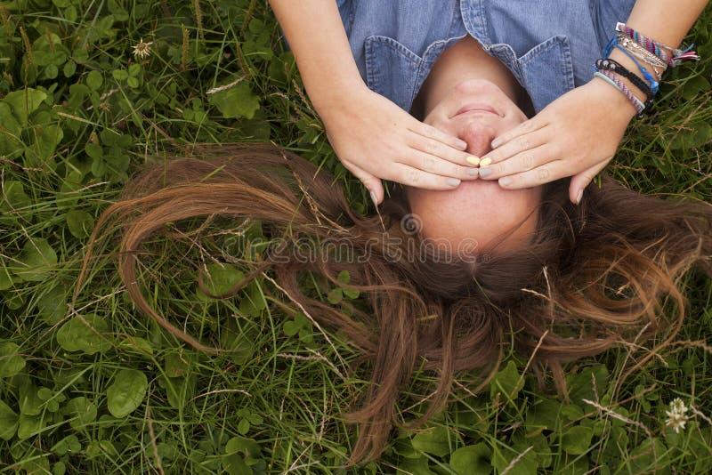 A menina bonita que encontra-se na grama fecha seus olhos com suas mãos Problemas dos adolescentes fotos de stock royalty free