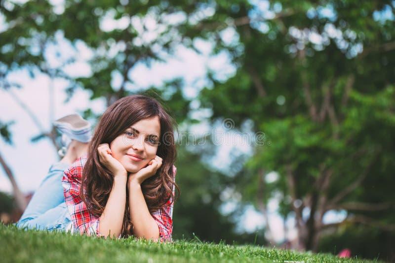 Menina bonita que encontra-se na grama verde fotografia de stock